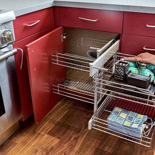 サンフランシスコの中くらいのモダンスタイルのおしゃれなキッチン (アンダーカウンターシンク、フラットパネル扉のキャビネット、赤いキャビネット、人工大理石カウンター、シルバーの調理設備、無垢フローリング、茶色い床、グレーのキッチンカウンター) の写真
