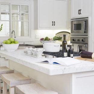 Идея дизайна: большая отдельная, п-образная кухня в современном стиле с техникой из нержавеющей стали, раковиной в стиле кантри, фасадами в стиле шейкер, белыми фасадами, столешницей из талькохлорита, белым фартуком, фартуком из каменной плитки, темным паркетным полом и островом