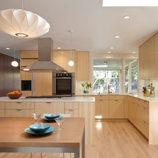 Minimalist l-shaped open concept kitchen photo in San Francisco with stainless steel appliances, an undermount sink, flat-panel cabinets, medium tone wood cabinets, quartz countertops and white backsplash