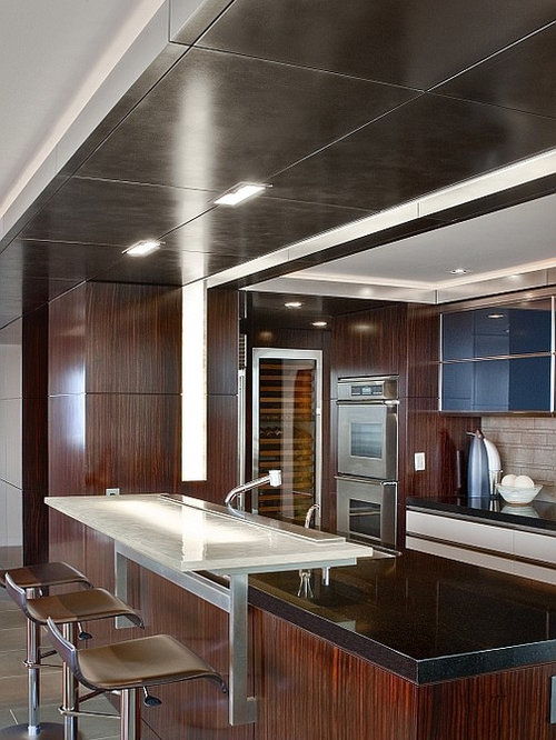 Trendy Kitchen Photo In Seattle With Stainless Steel Appliances, Glass  Countertops And Black Countertops