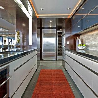 シアトルのインダストリアルスタイルのおしゃれなキッチン (アンダーカウンターシンク、フラットパネル扉のキャビネット、白いキャビネット、ベージュキッチンパネル、シルバーの調理設備の) の写真