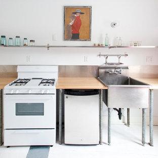 Ispirazione per una cucina lineare industriale con lavello stile country e elettrodomestici bianchi