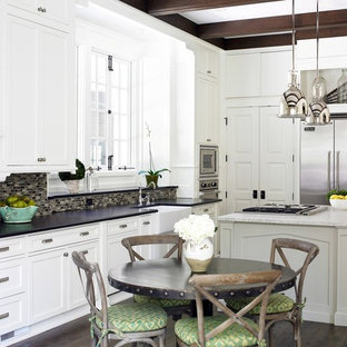 Mid-sized transitional eat-in kitchen ideas - Mid-sized transitional l-shaped dark wood floor eat-in kitchen photo in Atlanta with stainless steel appliances, a farmhouse sink, white cabinets, black backsplash, glass tile backsplash, granite countertops, shaker cabinets and an island