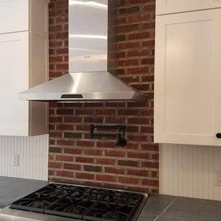 シンシナティの中サイズのカントリー風おしゃれなアイランドキッチン (白いキャビネット、人工大理石カウンター、赤いキッチンパネル、レンガのキッチンパネル、シルバーの調理設備) の写真