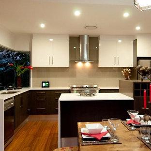 サンシャインコーストの中サイズのアジアンスタイルのおしゃれなキッチン (ダブルシンク、フラットパネル扉のキャビネット、濃色木目調キャビネット、人工大理石カウンター、ベージュキッチンパネル、ガラス板のキッチンパネル、シルバーの調理設備の、竹フローリング) の写真