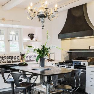 サンタフェスタイルのおしゃれなキッチン (エプロンフロントシンク、フラットパネル扉のキャビネット、白いキャビネット、マルチカラーのキッチンパネル、黒い調理設備、黒い床、白いキッチンカウンター) の写真