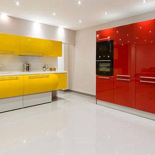 他の地域の中サイズのモダンスタイルのおしゃれなキッチン (アンダーカウンターシンク、黄色いキャビネット、人工大理石カウンター、黄色いキッチンパネル、ガラス板のキッチンパネル、黒い調理設備、磁器タイルの床) の写真