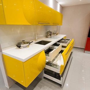Modelo de cocina en L, minimalista, de tamaño medio, abierta, con fregadero bajoencimera, puertas de armario amarillas, encimera de acrílico, salpicadero amarillo, salpicadero de vidrio templado, electrodomésticos negros y suelo de baldosas de porcelana