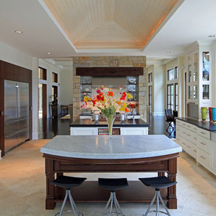 Photo of a contemporary kitchen in St Louis with stainless steel appliances, a triple-bowl sink, white cabinets, travertine floors and multiple islands.