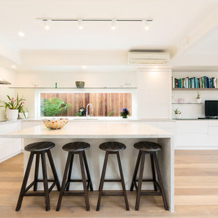 Contemporary l-shaped eat-in kitchen in Melbourne with an undermount sink, flat-panel cabinets, white cabinets, white splashback, window splashback, light hardwood floors, with island, beige floor and white benchtop.