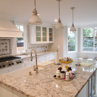 Mid-sized transitional eat-in kitchen inspiration - Eat-in kitchen - mid-sized transitional single-wall eat-in kitchen idea with a farmhouse sink, recessed-panel cabinets, white cabinets, granite countertops, multicolored backsplash, porcelain backsplash, paneled appliances, an island and multicolored countertops
