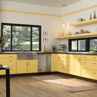 ニューヨークの大きいシャビーシック調のおしゃれなキッチン (エプロンフロントシンク、黄色いキャビネット、シルバーの調理設備の、淡色無垢フローリング、フラットパネル扉のキャビネット、御影石カウンター、アイランドなし) の写真
