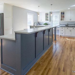 Bild på ett funkis kök, med skåp i shakerstil, gula skåp, vitt stänkskydd, rostfria vitvaror, mellanmörkt trägolv och en köksö