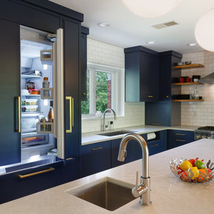 This is an example of a midcentury kitchen in Cincinnati with an undermount sink, flat-panel cabinets, blue cabinets, white splashback, cork floors and with island.