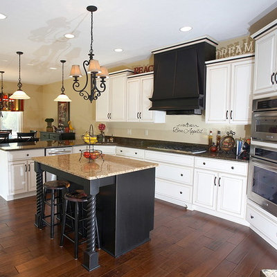 Mid-sized eclectic l-shaped dark wood floor eat-in kitchen photo in Indianapolis with a single-bowl sink, raised-panel cabinets, white cabinets, granite countertops, stainless steel appliances, an island and beige backsplash