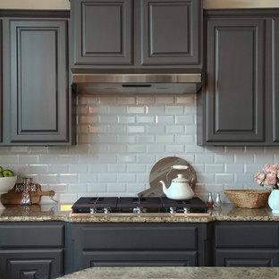 オースティンの大きいカントリー風おしゃれなキッチン (アンダーカウンターシンク、レイズドパネル扉のキャビネット、グレーのキャビネット、御影石カウンター、白いキッチンパネル、サブウェイタイルのキッチンパネル、シルバーの調理設備の、淡色無垢フローリング、ベージュのキッチンカウンター) の写真