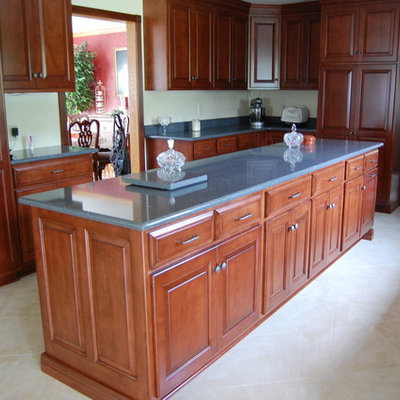 Transitional marble floor enclosed kitchen photo in Other with raised-panel cabinets, medium tone wood cabinets, granite countertops, beige backsplash, subway tile backsplash, stainless steel appliances and an island