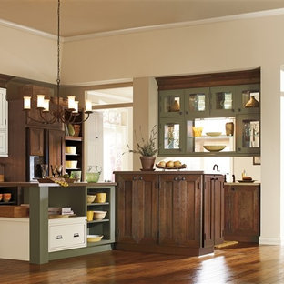 This is an example of a traditional single-wall kitchen/diner in Orange County with shaker cabinets, dark wood cabinets, beige splashback, ceramic splashback, medium hardwood flooring and multiple islands.