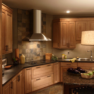 This is an example of a large country separate kitchen in Chicago with a double-bowl sink, raised-panel cabinets, medium wood cabinets, granite benchtops, grey splashback, slate splashback, stainless steel appliances, slate floors, with island and grey floor.