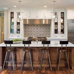 Zweizeilige Klassische Küche mit Schrankfronten im Shaker-Stil, hellbraunen Holzschränken, bunter Rückwand, Küchengeräten aus Edelstahl, braunem Holzboden, Kücheninsel, braunem Boden und weißer Arbeitsplatte in Minneapolis