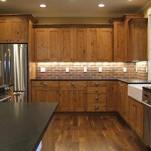 Exempel på ett rustikt kök, med rostfria vitvaror, en rustik diskho, luckor med infälld panel, skåp i mellenmörkt trä och rött stänkskydd
