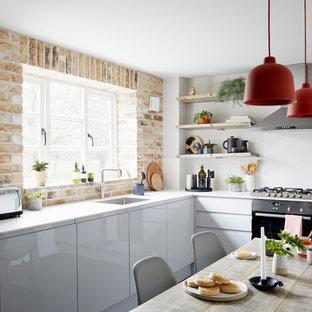 ロンドンのコンテンポラリースタイルのおしゃれなキッチン (シルバーの調理設備の、シングルシンク、フラットパネル扉のキャビネット、レンガのキッチンパネル、白いキッチンカウンター、グレーのキャビネット) の写真