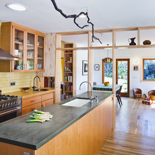 Design ideas for a contemporary kitchen in San Francisco with glass-front cabinets, concrete benchtops, stainless steel appliances, a single-bowl sink, medium wood cabinets, yellow splashback and subway tile splashback.