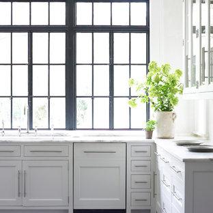Modelo de cocina tradicional renovada con armarios con paneles empotrados y puertas de armario blancas