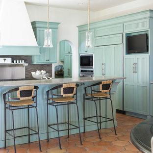 Bild på ett maritimt kök, med blå skåp, grått stänkskydd och integrerade vitvaror