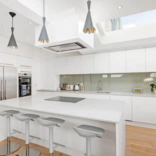 This is an example of a contemporary l-shaped open plan kitchen in London with a submerged sink, flat-panel cabinets, white cabinets, grey splashback, glass sheet splashback, stainless steel appliances, light hardwood flooring, an island and brown floors.