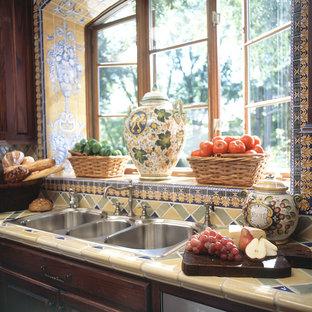 Geräumige Mediterrane Küche in U-Form mit Triple-Waschtisch, profilierten Schrankfronten, Schränken im Used-Look, Arbeitsplatte aus Fliesen, bunter Rückwand, Rückwand aus Porzellanfliesen, Küchengeräten aus Edelstahl und braunem Holzboden in Dallas