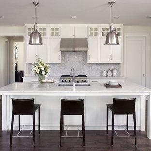Klassische Küche mit Marmor-Arbeitsplatte, weißen Schränken, Rückwand aus Steinfliesen, Küchengeräten aus Edelstahl, Unterbauwaschbecken, Schrankfronten mit vertiefter Füllung, dunklem Holzboden und Küchenrückwand in Grau in Minneapolis