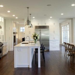 Immagine di una cucina abitabile classica con elettrodomestici in acciaio inossidabile, top in marmo, ante bianche, paraspruzzi grigio, paraspruzzi con piastrelle in pietra, lavello sottopiano, ante con riquadro incassato, parquet scuro e top bianco