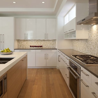 Example of a trendy kitchen design in Minneapolis with a double-bowl sink, solid surface countertops, flat-panel cabinets, white cabinets and mosaic tile backsplash
