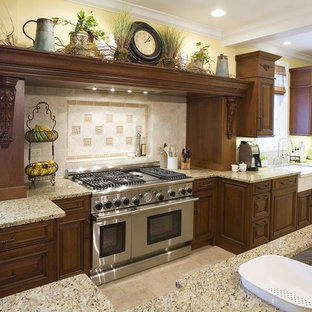 Rustic kitchen designs - Example of a mountain style kitchen design in Chicago with an undermount sink, raised-panel cabinets, dark wood cabinets, beige backsplash and stainless steel appliances