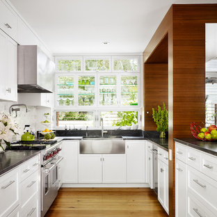 Inspiration for a midcentury kitchen in Austin with stainless steel appliances, a farmhouse sink, recessed-panel cabinets, white cabinets, white splashback and stone tile splashback.