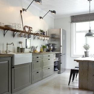 Esempio di una cucina abitabile country con ante con bugna sagomata, ante grigie, elettrodomestici in acciaio inossidabile, top in quarzo composito e pavimento in legno verniciato