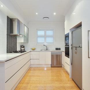 Geschlossene, Mittelgroße Moderne Küche in U-Form mit Einbauwaschbecken, flächenbündigen Schrankfronten, weißen Schränken, Küchenrückwand in Weiß, Küchengeräten aus Edelstahl, Quarzwerkstein-Arbeitsplatte, Rückwand aus Keramikfliesen, Bambusparkett, beigem Boden und weißer Arbeitsplatte in Sydney