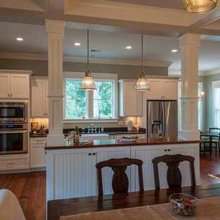 This is an example of a mid-sized country single-wall eat-in kitchen in Charleston with stainless steel appliances, medium hardwood floors, with island, a farmhouse sink, louvered cabinets, white cabinets and wood benchtops.