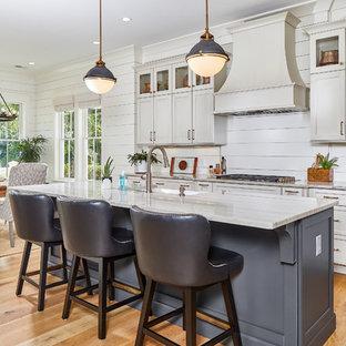 チャールストンの広いビーチスタイルのおしゃれなキッチン (シェーカースタイル扉のキャビネット、ベージュのキャビネット、白いキッチンパネル、淡色無垢フローリング、マルチカラーのキッチンカウンター、ドロップインシンク、木材のキッチンパネル、シルバーの調理設備、茶色い床、珪岩カウンター) の写真