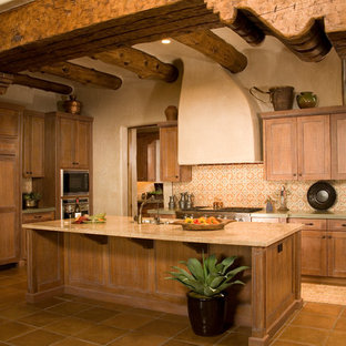 Mediterranean kitchen designs - Tuscan kitchen photo in Seattle with shaker cabinets, medium tone wood cabinets, multicolored backsplash and paneled appliances