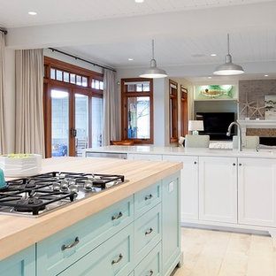 Design ideas for a mid-sized beach style l-shaped open plan kitchen in Vancouver with an undermount sink, shaker cabinets, turquoise cabinets, quartzite benchtops, glass tile splashback, stainless steel appliances, porcelain floors and multiple islands.