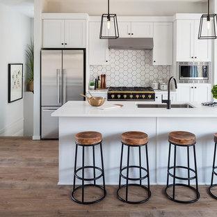 Idéer för att renovera ett litet lantligt vit vitt kök, med en undermonterad diskho, skåp i shakerstil, vita skåp, bänkskiva i kvartsit, vitt stänkskydd, stänkskydd i porslinskakel, rostfria vitvaror, laminatgolv, en köksö och brunt golv