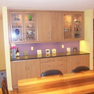 シンシナティのコンテンポラリースタイルのおしゃれなキッチン (アンダーカウンターシンク、中間色木目調キャビネット、御影石カウンター、シルバーの調理設備の、無垢フローリング、フラットパネル扉のキャビネット、ピンクのキッチンパネル) の写真