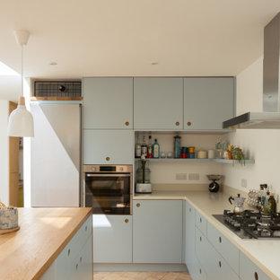 Bild på ett mellanstort funkis beige beige kök, med en integrerad diskho, släta luckor, blå skåp, bänkskiva i koppar, vitt stänkskydd, rostfria vitvaror, klinkergolv i terrakotta, en köksö och rosa golv