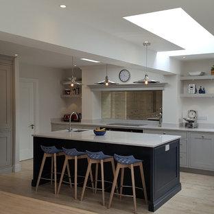 Moderne Wohnküche in L-Form mit Einbauwaschbecken, Schrankfronten mit vertiefter Füllung, Marmor-Arbeitsplatte, Küchenrückwand in Metallic, Rückwand aus Spiegelfliesen, Elektrogeräten mit Frontblende, Porzellan-Bodenfliesen und Kücheninsel in Dublin