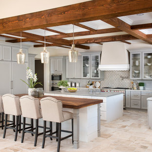 Inspiration for a large mediterranean l-shaped open plan kitchen in Phoenix with grey cabinets, wood benchtops, grey splashback, stainless steel appliances, multiple islands, beige floor, a farmhouse sink, recessed-panel cabinets, ceramic splashback and ceramic floors.