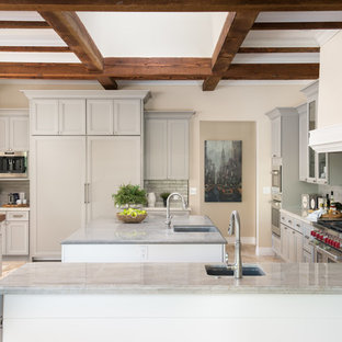 Large mediterranean l-shaped open plan kitchen in Phoenix with a farmhouse sink, recessed-panel cabinets, grey cabinets, ceramic splashback, stainless steel appliances, multiple islands, beige floor, wood benchtops, grey splashback and ceramic floors.
