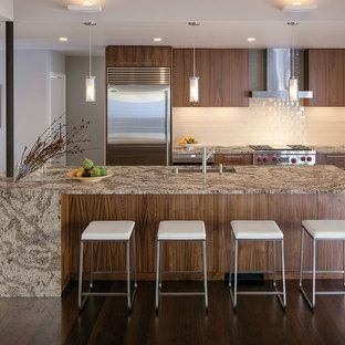 Zweizeilige, Offene Moderne Küche mit Unterbauwaschbecken, dunklen Holzschränken, Quarzwerkstein-Arbeitsplatte, Küchenrückwand in Weiß, Küchengeräten aus Edelstahl, dunklem Holzboden, Kücheninsel, flächenbündigen Schrankfronten, Rückwand aus Glasfliesen, braunem Boden und brauner Arbeitsplatte in New York