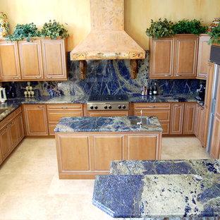 Новый формат декора квартиры: п-образная кухня среднего размера в стиле фьюжн с врезной раковиной, фасадами с выступающей филенкой, светлыми деревянными фасадами, мраморной столешницей, синим фартуком, полом из керамической плитки, островом, обеденным столом, техникой под мебельный фасад, бежевым полом, фартуком из каменной плиты и синей столешницей